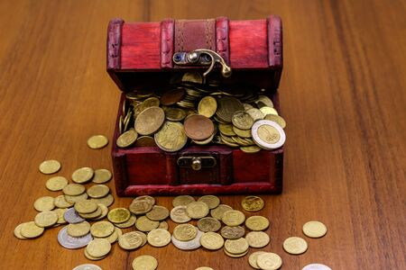 Vintage treasure chest full of golden coins on wooden background Zdjęcie Seryjne