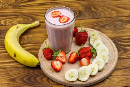 Glass of fresh smoothie of strawberry and banana on a wooden table Banque d'images - 130815925