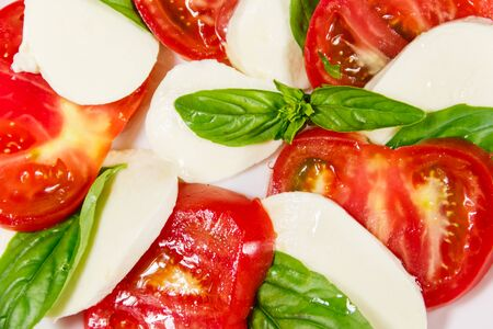 Italian caprese salad with tomatoes, mozzarella cheese and basil. Close-up
