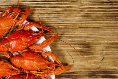 Boiled crayfish in plate on wooden table. Top view Stockfoto