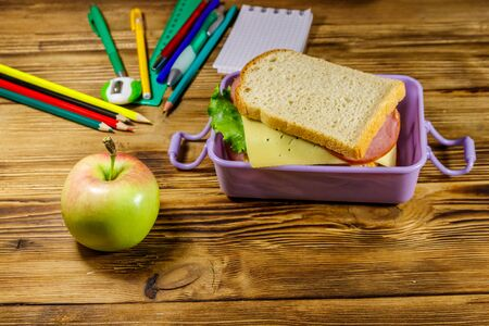 Back to school concept. School supplies, apple and lunch box with sandwiches on a wooden desk