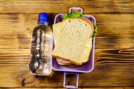 Lunch box with sandwiches and bottle of water on a wooden table. Top view