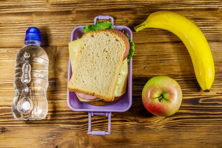 Lunch box with sandwiches, bottle of water, banana and apple on a wooden table. Top view Banque d'images