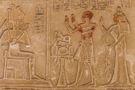 Peintures et hiéroglyphes égyptiens antiques découpés sur le mur en pierre
