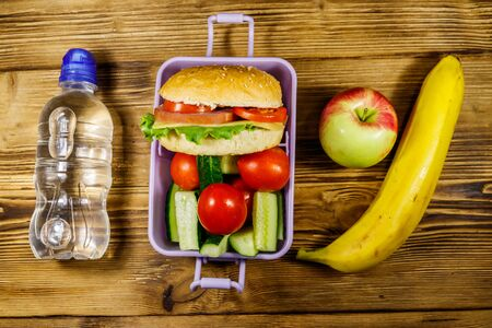 Bottle of water, apple, banana and lunch box with burgers and fresh vegetables on a wooden table. Top view Banque d'images