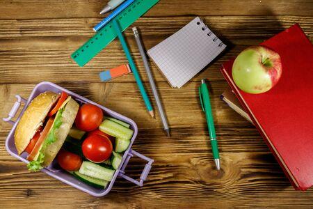 学校のコンセプトに戻る。木製のテーブルの上にハンバーガーと新鮮な野菜を入れた学用品、本、リンゴ、弁当箱。トップビュー 写真素材