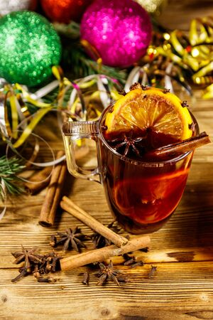 Christmas mulled wine with spices and Christmas decoration on wooden table