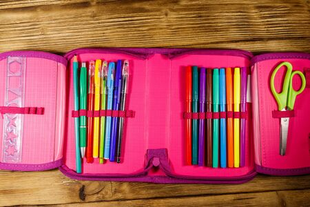 Pencil case containing pens, pencils, felt-tip pens, scissors and ruler on wooden desk. Top view