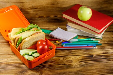 Back to school concept. School supplies, books, apple and lunch box with sandwiches and fresh vegetables on a wooden desk