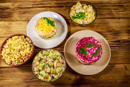 Set of festive mayonnaise salads on wooden table