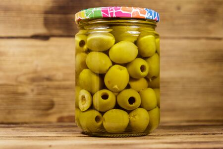 Pickled green olives in glass jar on wooden table