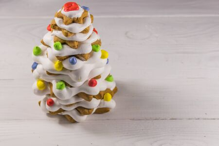 Gingerbread Christmas tree decorated with glaze on white wooden table