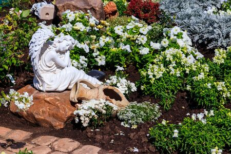 White marble statue of angel in ornamental garden