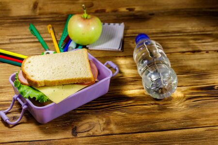 Back to school concept. School supplies, bottle of water, apple and lunch box with sandwiches on a wooden desk
