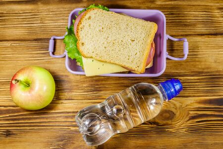 Lunch box with sandwiches, bottle of water and apple on a wooden table. Top view