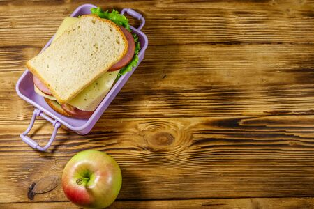 Lunch box with sandwiches and apple on a wooden table. Top view, copy space Reklamní fotografie
