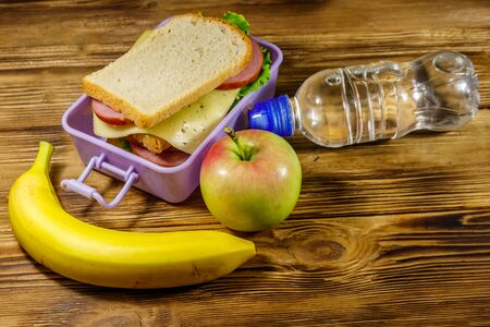 Lunch box with sandwiches, bottle of water, banana and apple on a wooden table