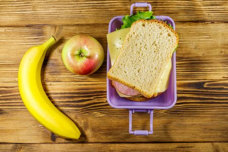 Lunch box with sandwiches, banana and apple on a wooden table. Top view Reklamní fotografie