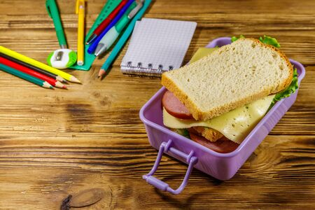 Back to school concept. School supplies and lunch box with sandwiches on a wooden desk