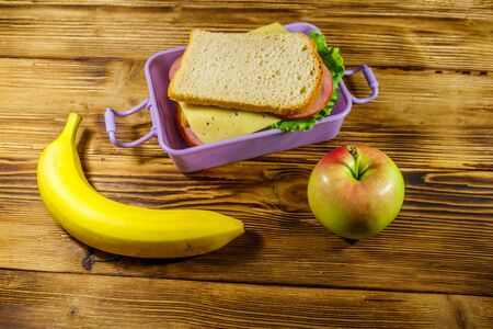 Lunch box with sandwiches, banana and apple on a wooden table