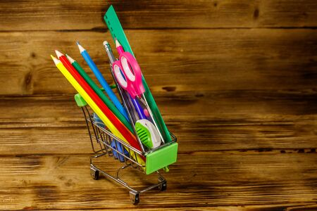 Buying school supplies. Shopping cart with school supplies on a wooden background. Back to school concept