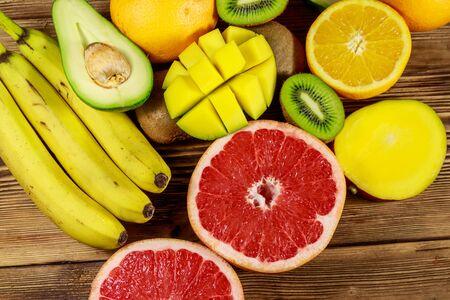 Assortment of tropical fruits on wooden table. Still life with bananas, mango, oranges, avocado, grapefruit and kiwi fruits