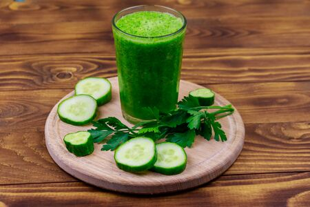 Glass of green detox smoothie of cucumber and parsley on a wooden table Stockfoto