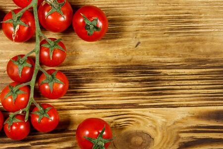 Fresh cherry tomatoes on a wooden table. Top view