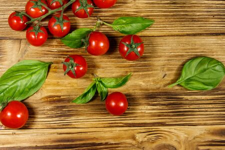 Fresh cherry tomatoes with green basil leaves on a wooden table. Top view