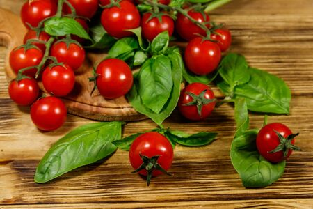 Fresh cherry tomatoes with green basil leaves on a wooden table