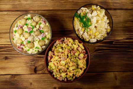 Set of festive mayonnaise salads on wooden table. Top view Reklamní fotografie