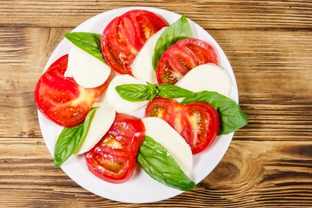 Italian caprese salad with tomatoes, mozzarella cheese and basil on a wooden table. Top view