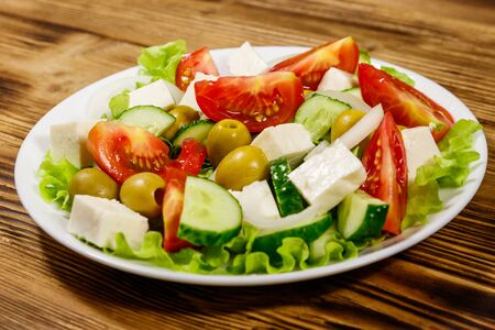 Greek salad with fresh vegetables, feta cheese and green olives on wooden table