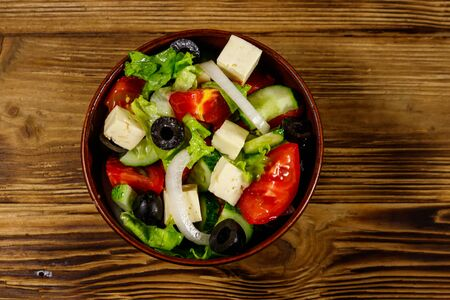 Greek salad with fresh vegetables, feta cheese and black olives on wooden table. Top view