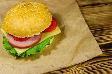 Fresh delicious homemade cheeseburger on brown paper on wooden table