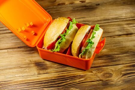 Lunch box with two homemade cheeseburgers on wooden table Stock fotó