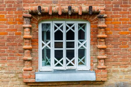 White wooden window on old red brick wall