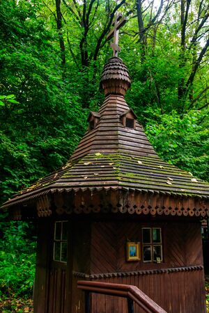 Small wooden orthodox chapel at holy spring in green forest in Shamordino, Kaluga Oblast, Russia