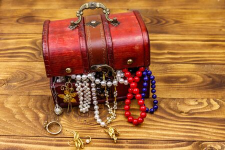 Vintage treasure chest full of jewelry and accessories on wooden background Фото со стока