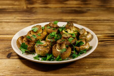 Baked mushrooms in plate on a wooden table