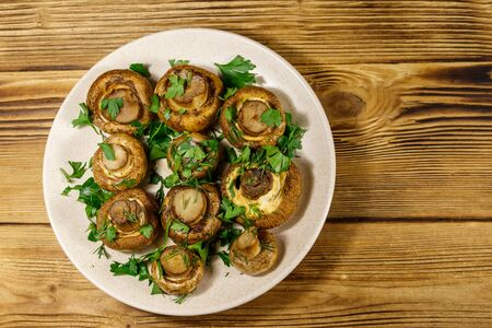 Baked mushrooms in plate on a wooden table. Top view Stockfoto