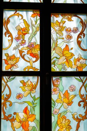 Old stained glass window with floral pattern in old cathedral