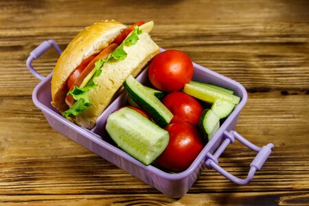 Lunch box with burgers and fresh vegetables on a wooden table Standard-Bild - 131993204