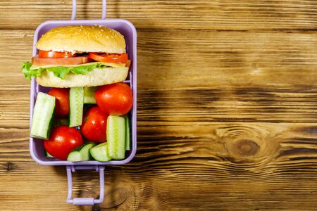 Lunch box with burgers and fresh vegetables on a wooden table. Top view, copy space Standard-Bild - 131992072