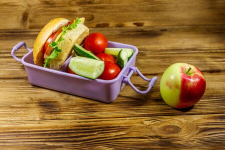 Apple and lunch box with burgers and fresh vegetables on a wooden table Standard-Bild - 131992988