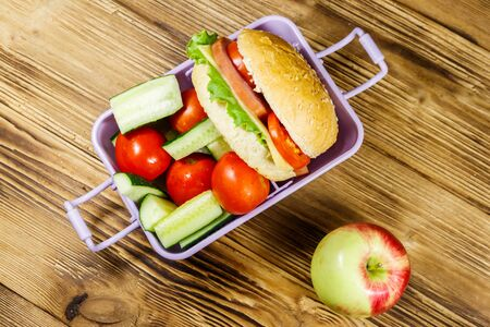 Apple and lunch box with burgers and fresh vegetables on a wooden table. Top view Standard-Bild - 131992938
