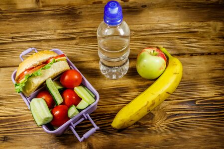 Bottle of water, apple, banana and lunch box with burgers and fresh vegetables on a wooden table Standard-Bild - 131993161