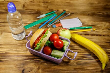 Back to school concept. School supplies, bottle of water, apple, banana and lunch box with burgers and fresh vegetables on a wooden table Standard-Bild - 131992416