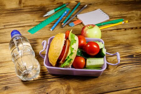 Back to school concept. School supplies, bottle of water, apple and lunch box with burgers and fresh vegetables on a wooden table Standard-Bild - 131993033