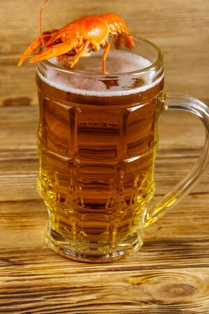Boiled crayfish and mug of beer on a wooden table Imagens